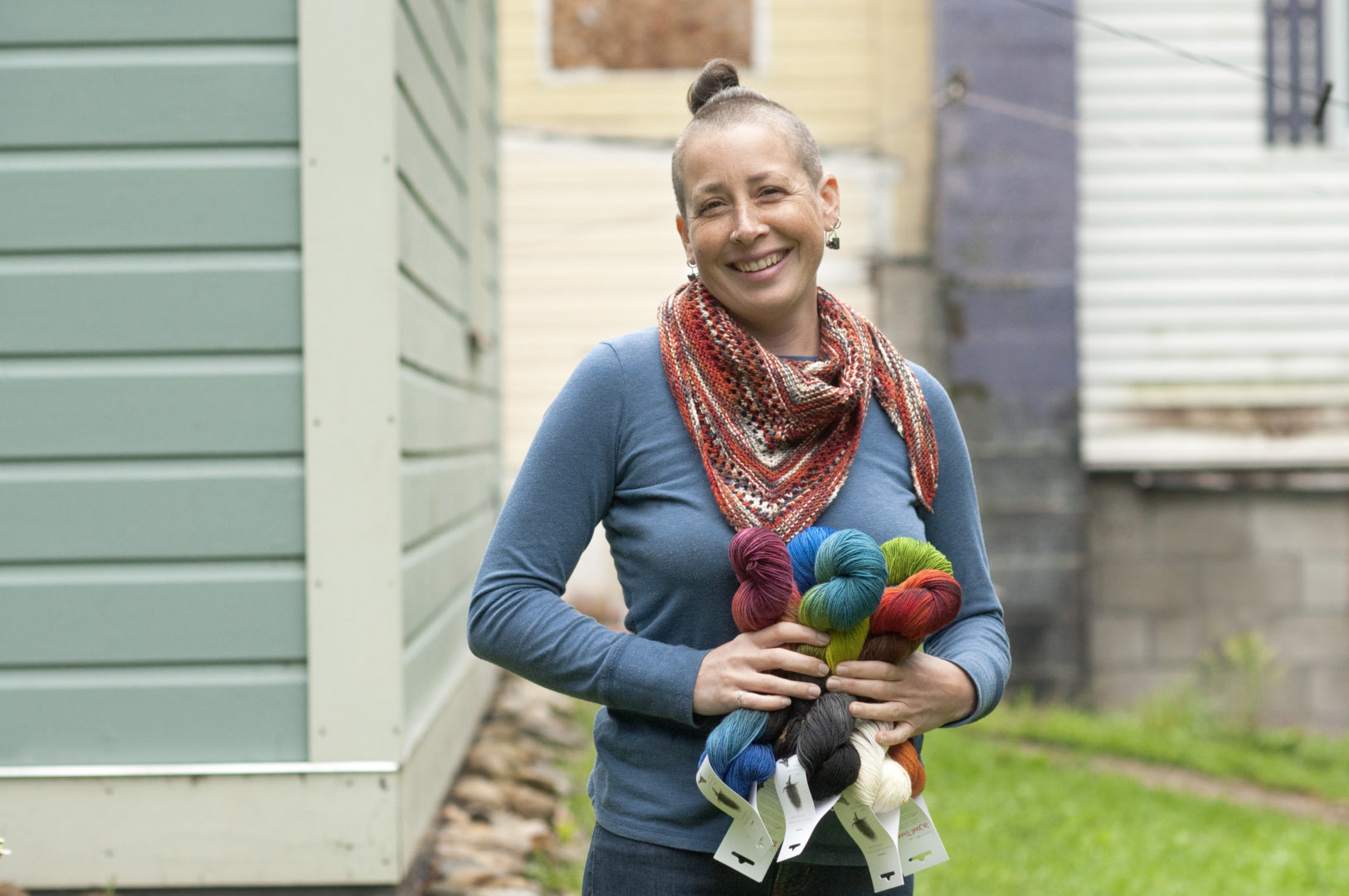 Monica MacNeille of Round Mountain fibers wears a blue sweater and jeans and poses with her hand-dyed, hand-spun yarns, holding skeins in a variety of blue, green and red shades