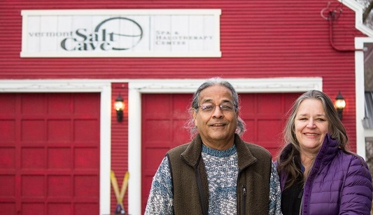 Sarita and Nafis Khan smile again the red barn exterior of the Vermont Salt Cave Spa & Halotherapy Center in Montgomerfy