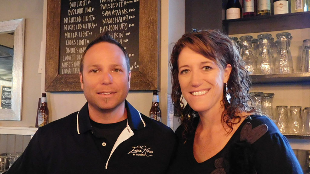 Dave and Melinda Gervais-Lamoureux where t-shirts with the Essex House logo and smile under the sign in the bar