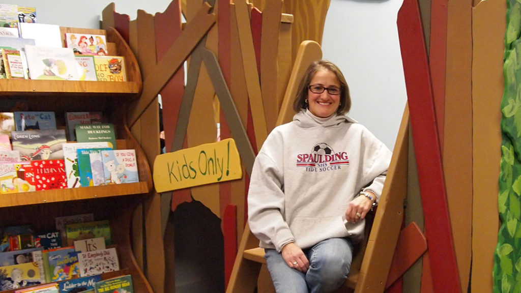 Cynthia Duprey of Next Chapter Bookstore wears a sweatshirt and jeans and poses by the treehouse in the children's reading area
