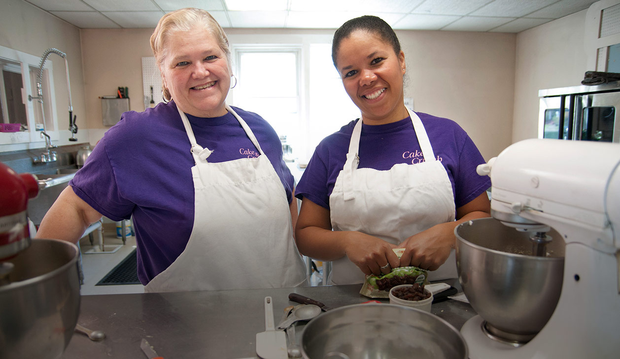 Julie Rogers and Susan Camley of Cake & Crumb Bakery in Morrisville pose in purple logo t-shirts with white aprons and a white mixer in the foreground
