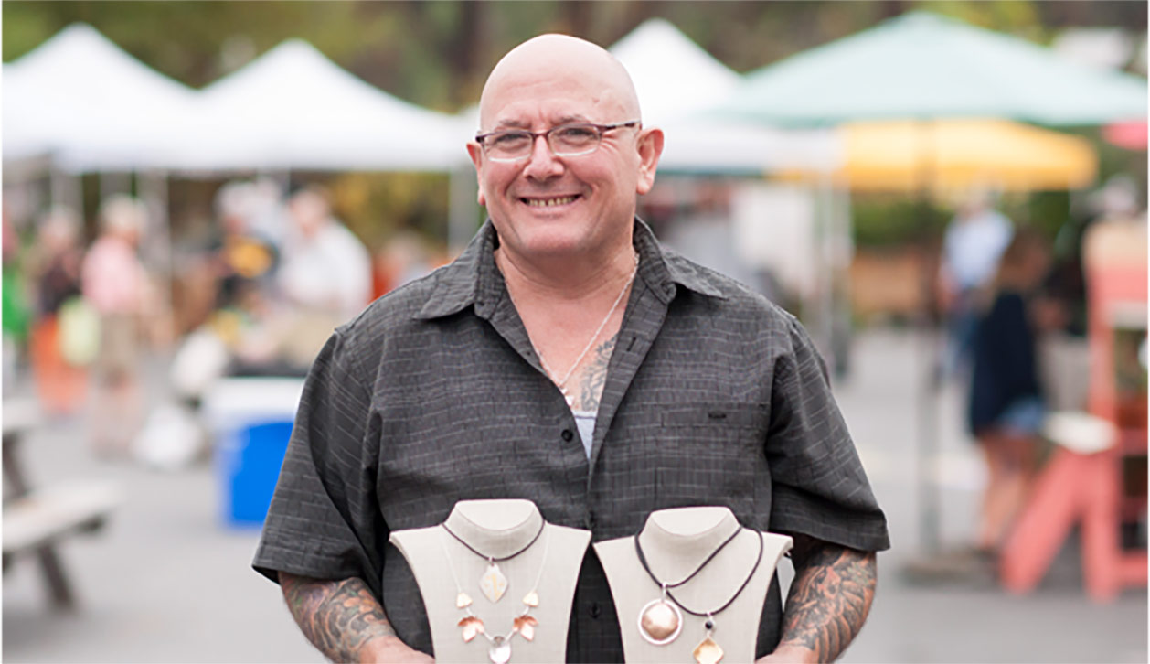 Dave Kaczynski of Khaos Designs hold a display of his handmade stone jewelry at a farmers market