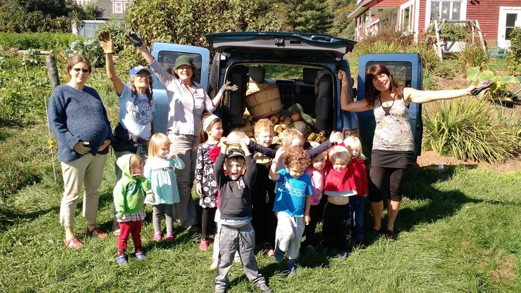 Women of AllTogetherNow! and a group of children stand in front of their blue van, open to show lots of fresh vegetables