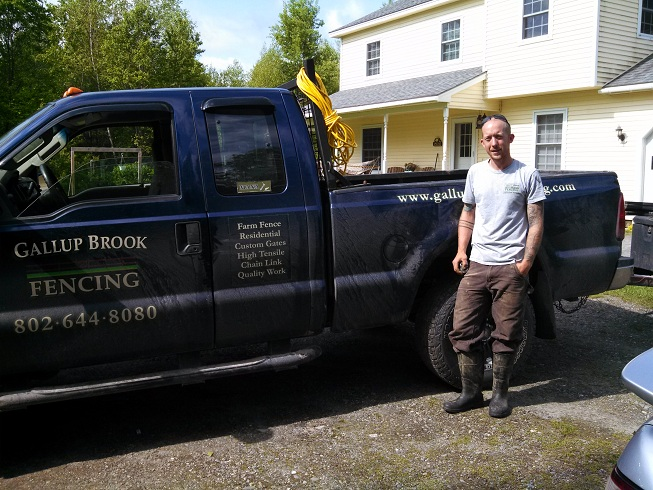 John Doyle of Gallup Brook Fencing stands in front of a blue pickup work truck