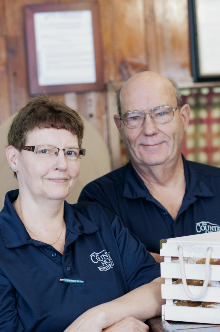 A man and a woman with glasses in blue shirts standing in a restaurant The Country House