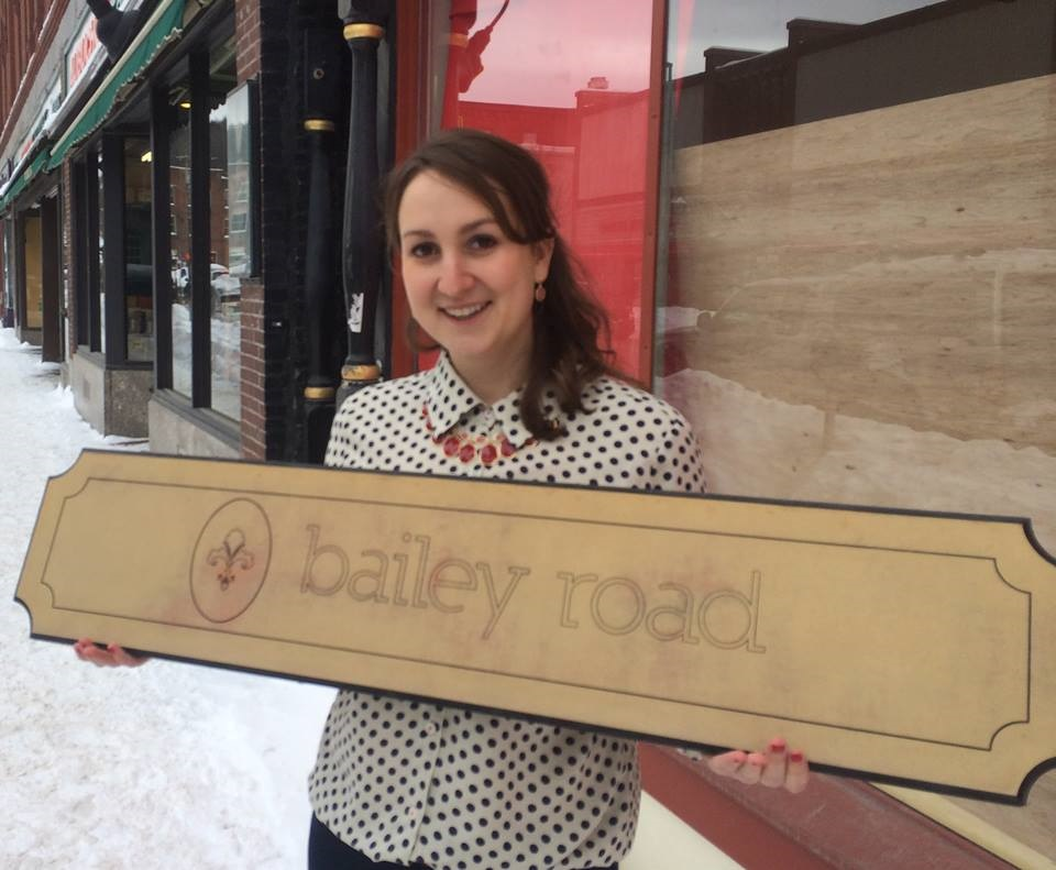 A young woman holds the sign to her new store, Bailey Road