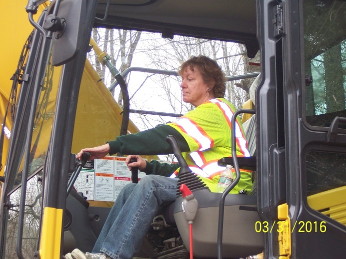 Michele Gaboriau of G & N Excavation in Middlesex wears a yellow vest and jeans while driving a tractor