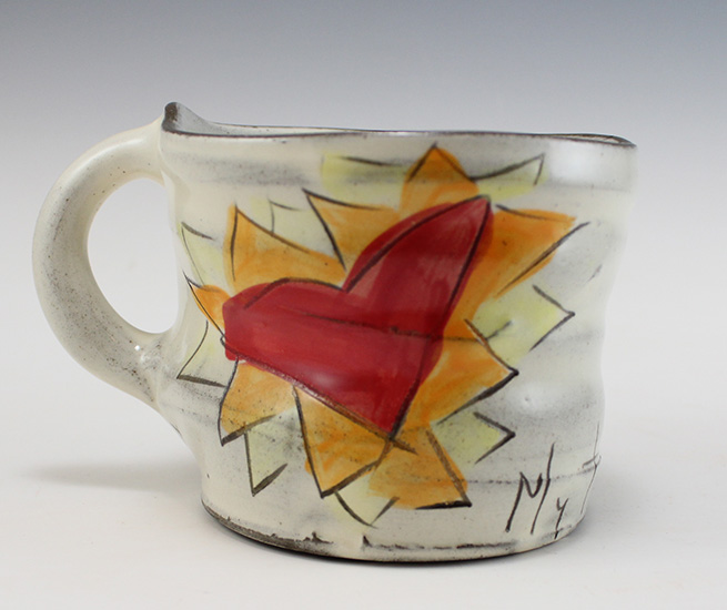 A close up of a handmade ceramic mug by Z-pots, featuring a red heart on an abstract orange and yellow background