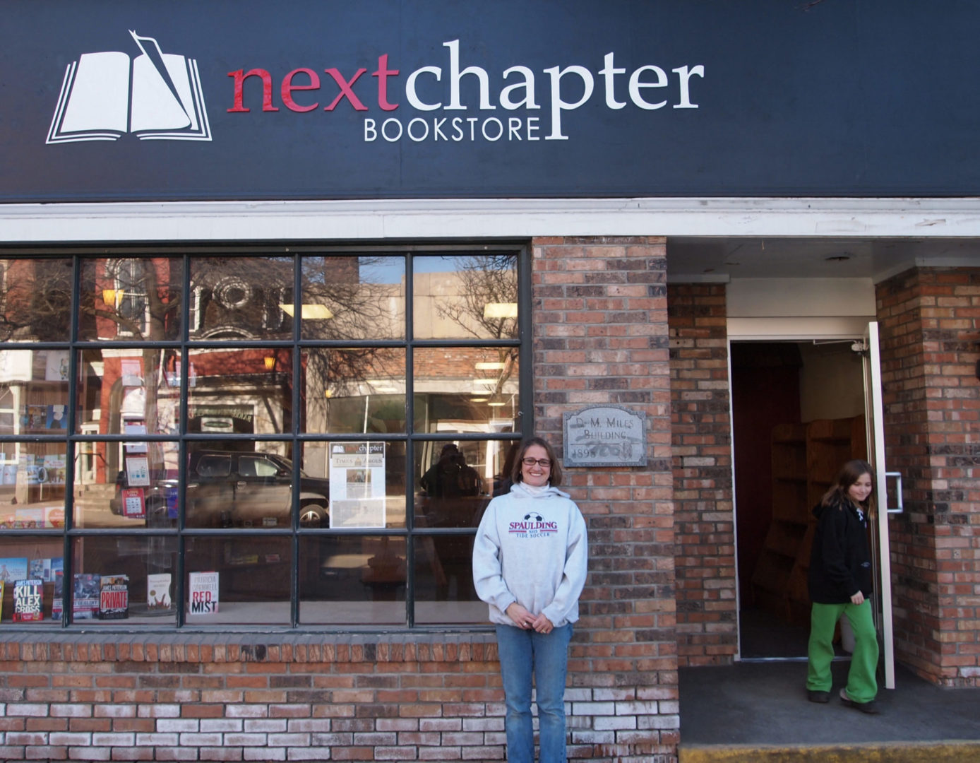 Cynthia Duprey of Next Chapter bookstore in Barre stands in front of her building, smiling, wearing a gray sweatshirt and jeans