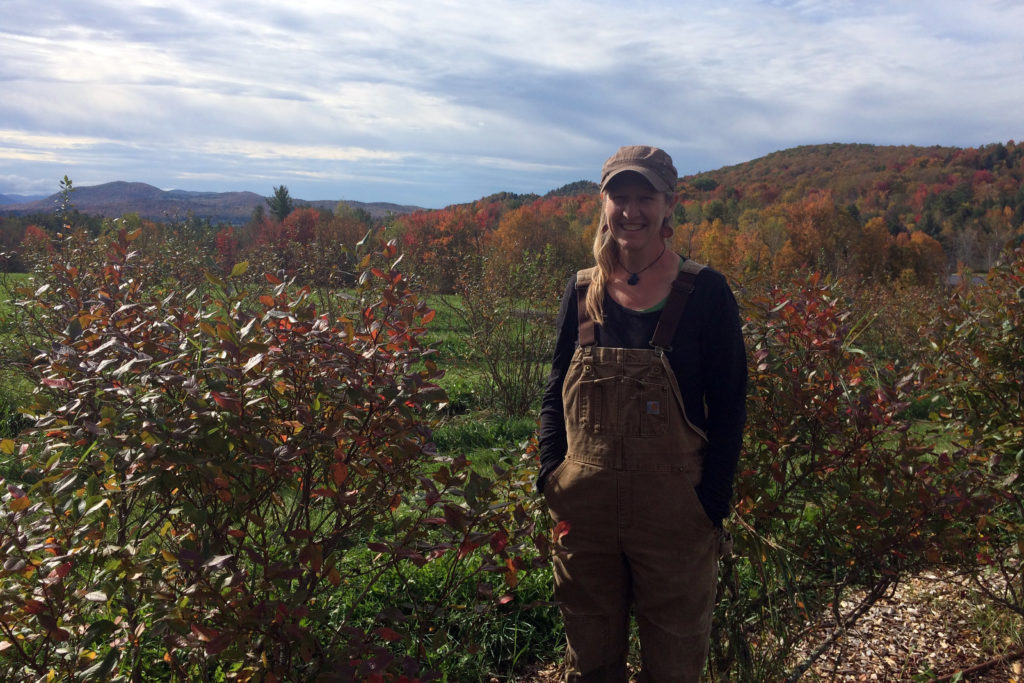 Holly Ferris of Wandering Roots Farm poses in front of her blueberry patch wearing brown overalls, a black shirt, and a ponytail with a cap