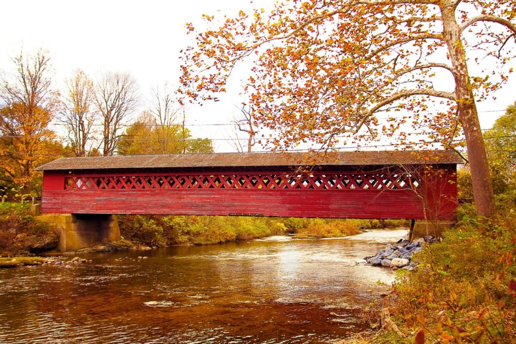 A beautiful red covered bridge spanning a serene creek, taken in the fall